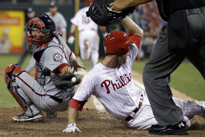 Kurt Suzuki tries to get Chase Utley out on a plate at the plate in the eighth inning but he is just late with the tag. The Nationals lost to the Phillies 3-1. (Associated Press photo)