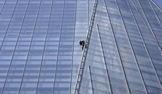 Greenpeace protesters climb up the Shard, the tallest building in Western Europe, on Thursday, July 11, 2013, in London during a protest against drilling in the Arctic by Royal Dutch Shell. (AP Photo/Sang Tan)