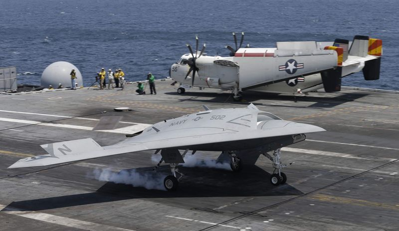 A X47-B Navy drone touches down as it lands aboard the nuclear aircraft carrier USS George H. W. Bush off the Coast of Virginia Wednesday, July 10, 2013. It is the first landing by a drone on a Navy carrier. (AP Photo/Steve Helber)