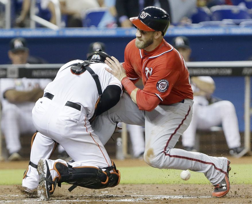 Bryce Harper collides with Marlins catcher Jeff Mathis to score for the Nationals on Saturday night. (Associated Press photo)