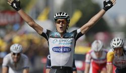 Matteo Trentin of Italy celebrates as he crosses the finish line to win the fourteenth stage of the Tour de France cycling race over 191 kilometers (119.4 miles) with start in in Saint-Pourcain-sur-Sioule and finish in Lyon, central France, Saturday July 13 2013. (AP Photo/Laurent Rebours)