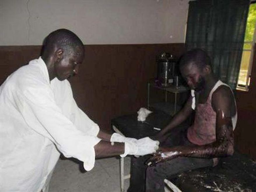 ** FILE ** A doctor attends to a student from Government Secondary School in Mamudo, at the Potiskum General Hospital, Nigeria, following an attack by gunmen on Saturday July 6, 2013. Islamic militants attacked a boarding school before dawn Saturday, dousing a dormitory in fuel and lighting it ablaze as students slept, survivors said.  (AP Photo/Adamu Adamu)