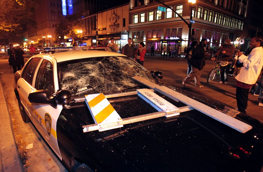 A BART police vehicle is vandalized early on Sunday, July 14, 2013, in Oakland, Calif., during a protest after George Zimmerman was found not guilty in the 2012 shooting death of teenager Trayvon Martin. Protesters angered by the verdict held largely peaceful demonstrations in three California cities but broke windows and started small street fires Oakland, police said. (AP Photo/Bay Area News Group, Anda Chu)