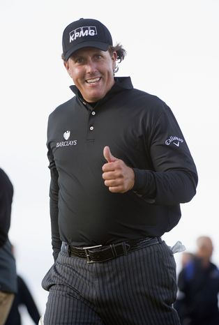 Phil Mickelson from the US, gestures, as he walks down to the 18th hole, during day four of the Scottish Open, at Castle Stuart Golf Course, in Inverness, Scotland, Sunday July 14, 2013. Phil Mickelson birdied the first playoff hole to beat Branden Grace and win the Scottish Open on Sunday, ending his 20-year wait for a victory in Europe. (AP Photo/PA, Kenny Smith)