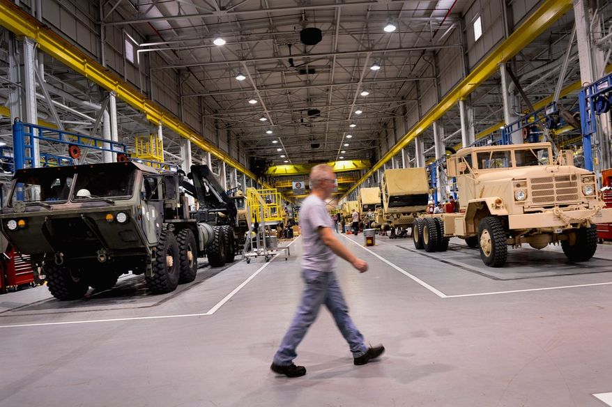 A worker walks past military vehicles as they are reassembled and repaired at Letterkenny Army Depot, Chambersburg, Pa., Thursday, April 4, 2013. The depot is anticipating layoffs and furloughs related to the federal budget cuts known as the sequester. (Andrew Harnik/The Washington Times)
