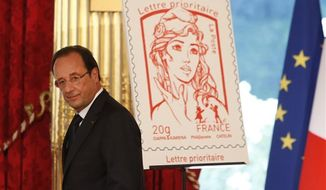 French President Francois Hollande stands next to the newly unveiled official Marianne postage stamp at the Elysee Palace during the Bastille Day celebrations in Paris. (AP Photo/Francois Mori, File)