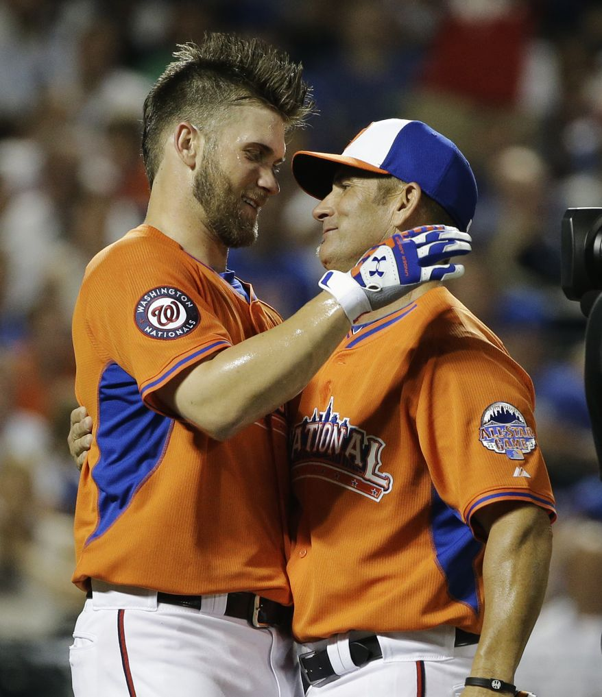 Bryce Harper, left, and his father, Ron, embrace after the Home Run Derby. (Associated Press photo)