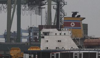 The North Korean-flagged cargo ship Chong Chon Gang (in yellow) sits docked at the Manzanillo International Container Terminal on the coast at Colon City, Panama, early on Tuesday, July 16, 2013. Panama's president said the country has seized the ship, which was carrying what appeared to be ballistic missiles and other arms. (AP Photo/Arnulfo Franco)