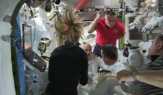 In this image from video made available by NASA, astronauts discuss the aborted spacewalk aboard the International Space Station on Tuesday, July 16, 2013. A dangerous water leak in the helmet of Luca Parmitano, bottom center facing camera in white suit, drenched his eyes, nose and mouth, preventing him from hearing or speaking as what should have been a routine spacewalk came to an abrupt end. (AP Photo/NASA)