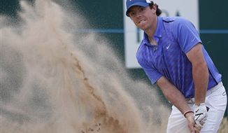 Rory McIlroy of Northern Ireland plays out of the bunker on the 18th hole during a practice round ahead of the British Open Golf Championship at Muirfield, Scotland, Wednesday July 17, 2013. (AP Photo/Peter Morrison)