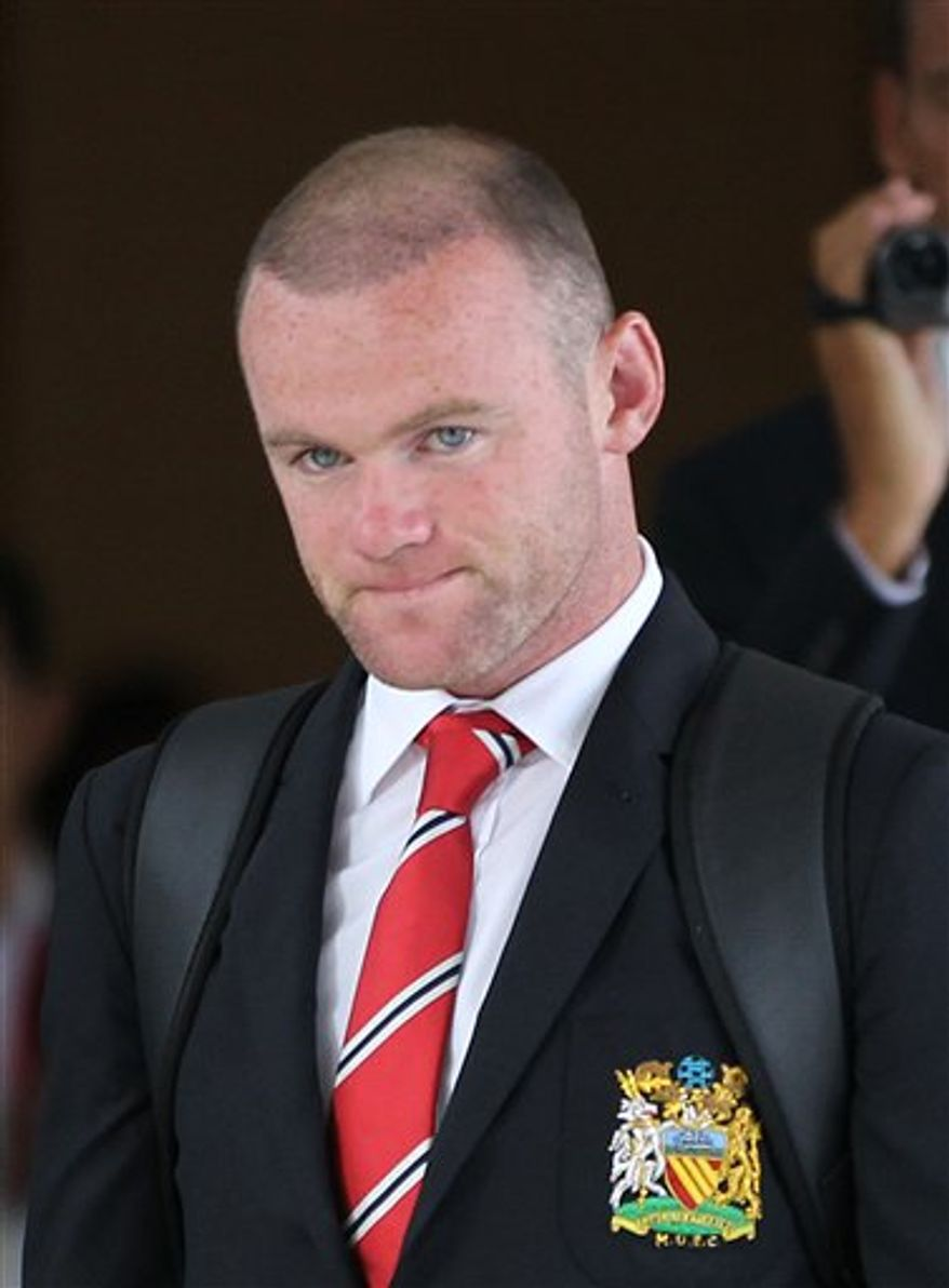 **FILE** In this photo taken July 11, 2013, Wayne Rooney of England and Manchester United football club, walks to a waiting coach after arriving at Don Muang international airport in Bangkok, Thailand. Manchester United said on Thursday that striker Rooney is flying back to England from the club's preseason tour of Asia because of injury, a day after arriving in the Thai capital. United said that Rooney injured a hamstring in training. (AP Photo/Apichart Weerawong)