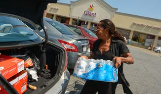 Phebie Warren, the director of the Little Busy Bee day care center in Ft. Washington, Md., loads her trunk with bottled water as a large portion of Prince George's County will be without water for the next 3-5 days as the Washington Suburban Sanitary Commission prepares to repair a 54-inch water line which is close to bursting, Ft. Washington, D.C., Tuesday, July 16, 2013. (Andrew Harnik/The Washington Times)