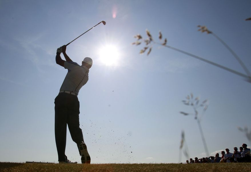 Tiger Woods of the United States plays a shot on the 15th hole during a practice round for the British Open Golf Championship at Muirfield, Scotland, Wednesday July 17, 2013. (AP Photo/Peter Morrison)