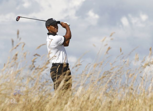 Tiger Woods of the United States plays a shot from the third tee during the first round of the British Open Golf Championship at Muirfield, Scotland, Thursday July 18, 2013. (AP Photo/Jon Super)