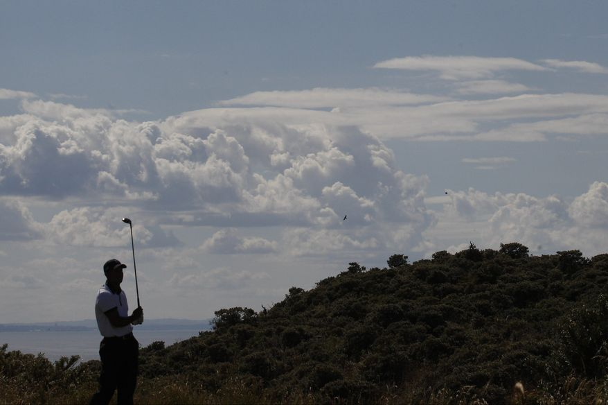 Rory McIlroy of Northern Ireland plays a shot onto the first green during the first round of the British Open Golf Championship at Muirfield, Scotland, Thursday July 18, 2013. (AP Photo/Peter Morrison)