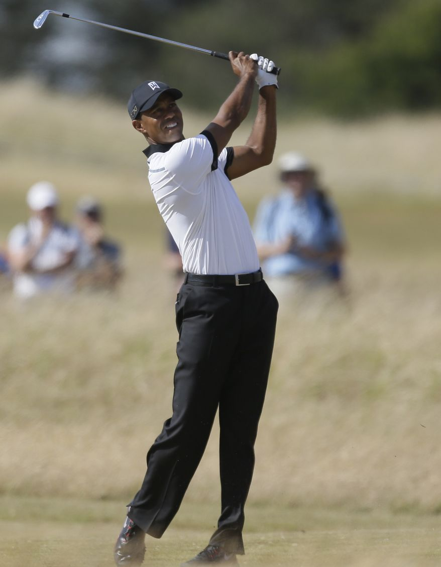 Tiger Woods of the United States plays out of the rough on the first fairway during the first round of the British Open Golf Championship at Muirfield, Scotland, Thursday July 18, 2013. (AP Photo/Jon Super)
