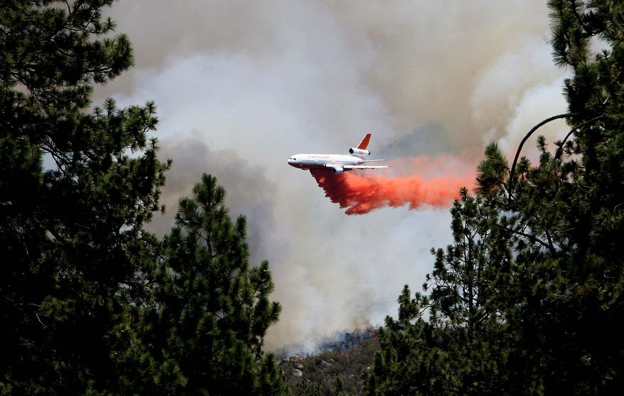 An air tanker makes a drop on the Mountain Fire near Lake Hemet, Calif., on Tuesday, July 16, 2013. The 14,200 acre forest fire near Idyllwild Calif., has caused Idyllwild and adjacent communities east of Highway 243 to issued mandatory evacuations for hundreds of homes Wednesday. (AP Photo/The Press-Enterprise, Frank Bellino)