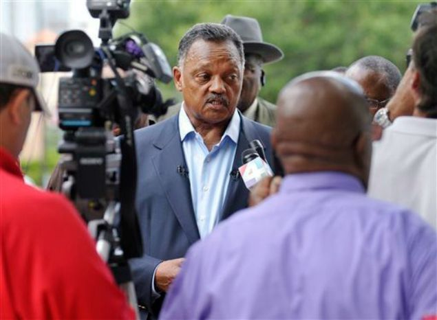 The Rev. Jesse Jackson, center, talks to the media outside the Duval County Jail Tuesday, July 16, 2013 in Jacksonville, Fla., after visiting Marissa Alexander, who is serving a 20-year sentence for firing a gun into the air to stop her abusive husband. (Associated Press)