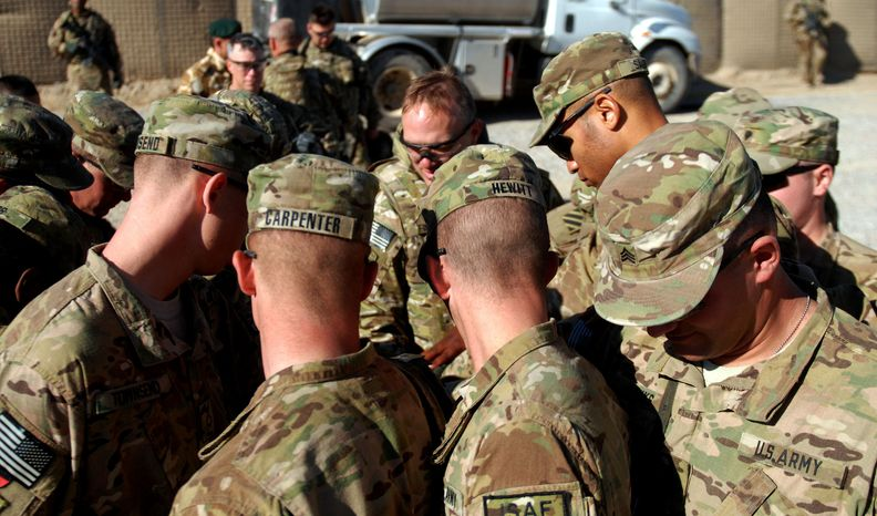 U.S. soldiers with Bravo Battery, 1st Battalion, 41st Field Artillery Regiment, 1st Brigade Combat Team, 3rd Infantry Division, bow their heads as Maj. Daniel Finkhousen, the brigade's chaplain, offers an invocation on Christmas Day at Forward Operating Base Al Masaak in Afghanistan's Zabul province on Tuesday, Dec. 25, 2012. (U.S. Army/1st Lt. Vanessa Macekura)