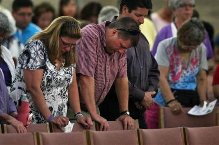 Worshipers attend a memorial mass held for supporters and families of those killed in the Aurora movie theater shootings, at St. Michael the Archangel Catholic Church, in Aurora, Colo., on Friday