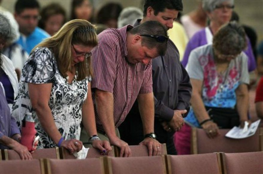 Worshipers attend a memorial mass held for supporters and families of those killed in the Aurora movie theater shootings, at St. Michael the Archangel Catholic Church, in Aurora, Colo., on Friday July 19, 2013. Saturday, July 20 marks one year since the theater killing rampage left 12 dead and 70 wounded. (AP Photo/Brennan Linsley)
