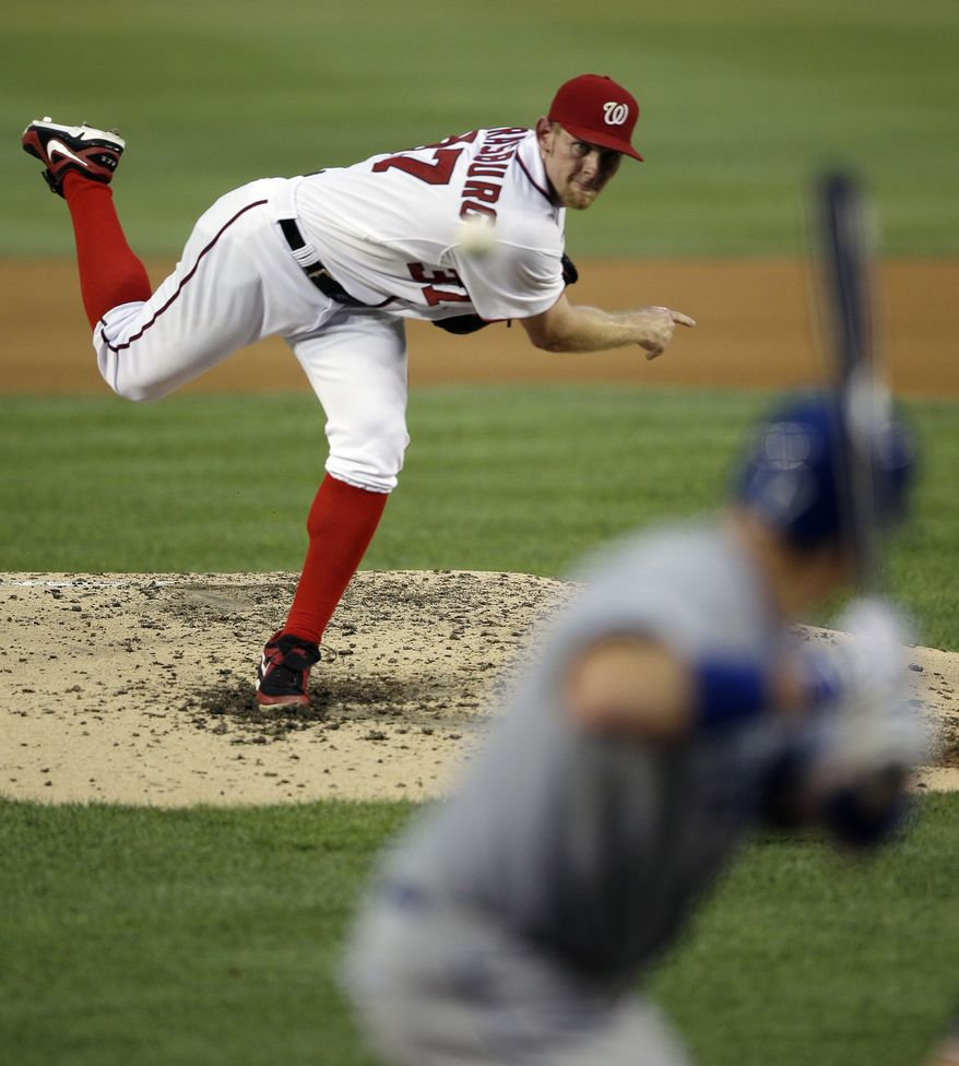 Washington Nationals starting pitcher Stephen Strasburg, top, delivers against Los Angeles Dodgers' A.J. Ellis during the fourth inning of a baseball game at Nationals Park, Friday, July 19, 2013, in Washington. (AP Photo/Pablo Martinez Monsivais)