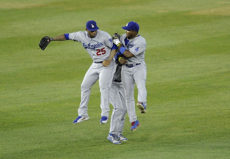Los Angeles Dodgers' Yasiel Puig, right, celebrates with teammates Carl Crawford (25) and Andre Ethier, back, after the Dodgers defeated the Washington Nationals 3-1 in 10 innings in a baseball game, Saturday, July 20, 2013, in Washington. (AP Photo/Nick Wass)
