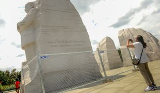 Earlene Purches of Flint, Mich., takes a photograph of the Martin Luther King Jr. Memorial on Monday. Work to remove a paraphrased quote from the memorial has begun and is expected to last three to four weeks. (Andrew Harnik/The Washington Times)