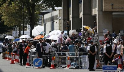 Members of media gather across from St Mary's Hospital Lindo Wing in London, Monday, July 22, 2013. Buckingham Palace officials say Prince William's wife, Kate, Duchess of Cambridge, has been admitted to St Mary's Hospital in the early stages of labour. Royal officials said that Kate traveled by car to St. Mary's Hospital in central London. Kate _ also known as the Duchess of Cambridge _ is expected to give birth in the private Lindo Wing of the hospital, where Princess Diana gave birth to William and his younger brother, Prince Harry.The baby will be third in line for the British throne _ behind Prince Charles and William _ and is anticipated eventually to become king or queen. (AP Photo/Sang Tan)