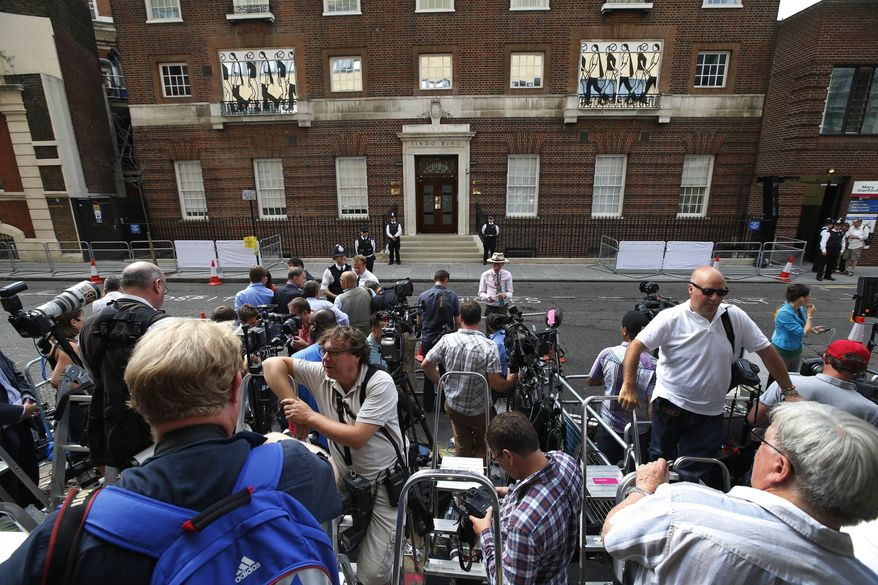 Members of the media wait across from St. Mary's Hospital exclusive Lindo Wing in London, Monday, July 22, 2013. Buckingham Palace officials say Prince William's wife, Kate, has been admitted to the hospital in the early stages of labour. Royal officials said that Kate traveled by car to St. Mary's Hospital in central London. Kate _ also known as the Duchess of Cambridge _ is expected to give birth in the private Lindo Wing of the hospital, where Princess Diana gave birth to William and his younger brother, Prince Harry. The baby will be third in line for the British throne _ behind Prince Charles and William _ and is anticipated eventually to become king or queen. (AP Photo/Lefteris Pitarakis)