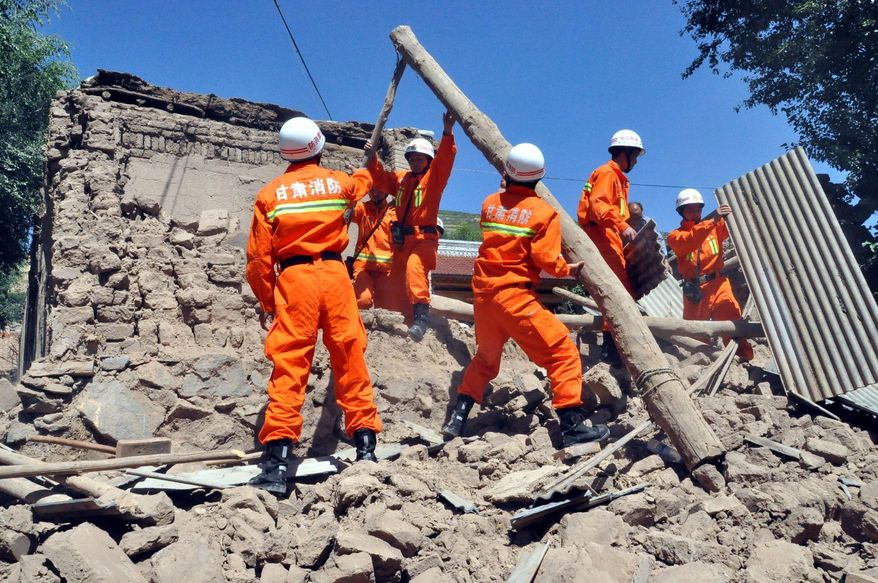 ** FILE ** In this photo released by Xinhua News Agency, rescuers clear the debris of a damaged house in quake-hit Majiagou Village of Minxian County, northwest China's Gansu Province, Monday, July 22, 2013. (AP Photo/Xinhua, Guo Gang)
