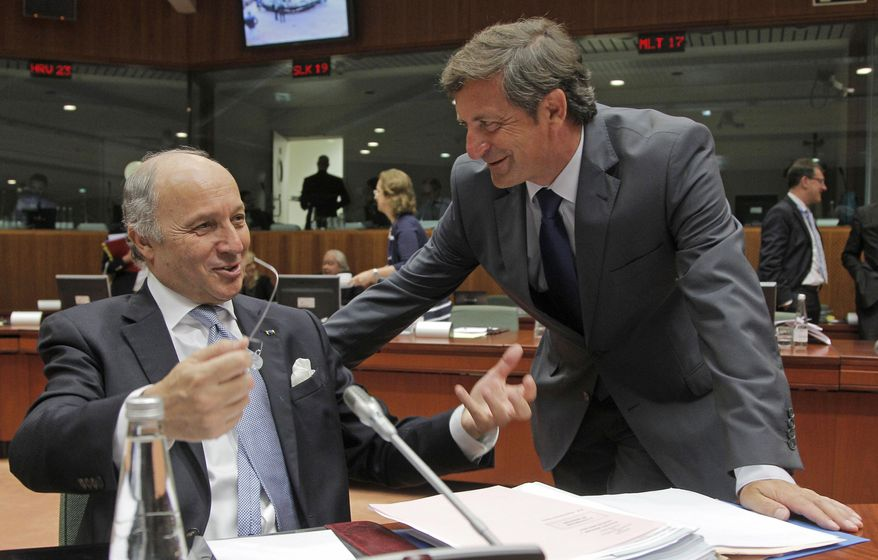 French Foreign Minister Laurent Fabius, left, talks with Slovenian Foreign Minister Karl Erjavec during the EU foreign ministers meeting at the European Council building in Brussels, Monday, July 22, 2013. (AP Photo/Yves Logghe)