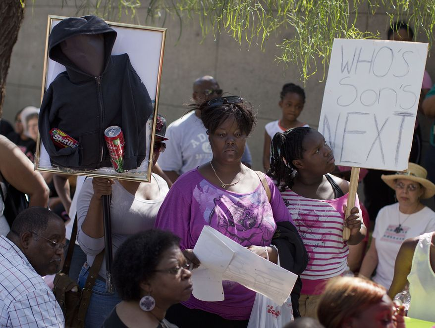 "Demonstrators listen to comments outside the Lloyd George Federal Courthouse during a ""Justice for Trayvon"" rally on Saturday, July 20, 2013, in Las Vegas. (AP Photo/Julie Jacobson)"