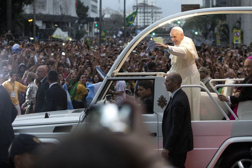 Pope Francis waves from his popemobile as he makes his way into central Rio de Janeiro, Brazil, Monday, July 22, 2013. The pontiff arrived for a seven-day visit in Brazil, the world's most populous Roman Catholic nation. During his visit, Francis will meet with legions of young Roman Catholics converging on Rio for the church's World Youth Day festival. (AP Photo/Felipe Dana)