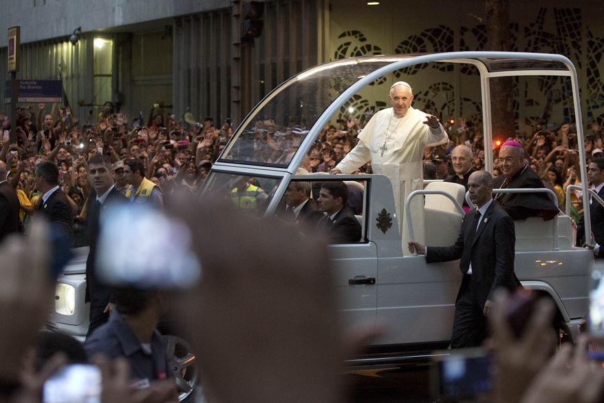 Pope Francis waves from his popemobile as he makes his way into central Rio de Janeiro, Brazil, Monday, July 22, 2013. The pontiff arrived for a seven-day visit in Brazil, the world's most populous Roman Catholic nation. During his visit, Francis will meet with legions of young Roman Catholics converging on Rio for the church's World Youth Day festival.(AP Photo/Felipe Dana)