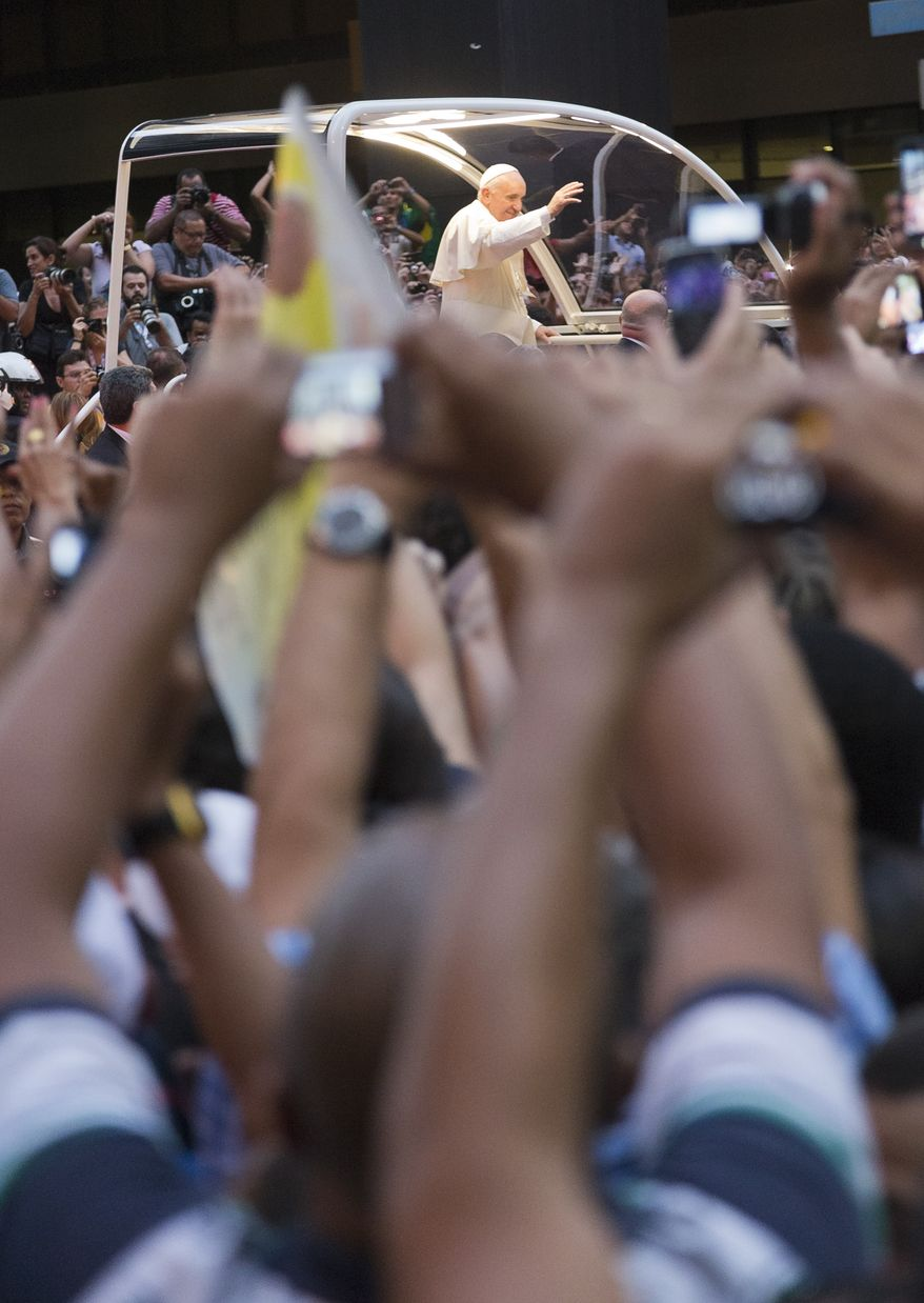 People wave to Pope Francis riding in a popemobile upon his arrival to Rio de Janeiro, Monday, July 22, 2013. Pope Francis returned to his home continent for the first time as pontiff, embarking on a seven-day visit meant to fan the fervor of the faithful around the globe. (AP Photo/Domenico Stinellis)