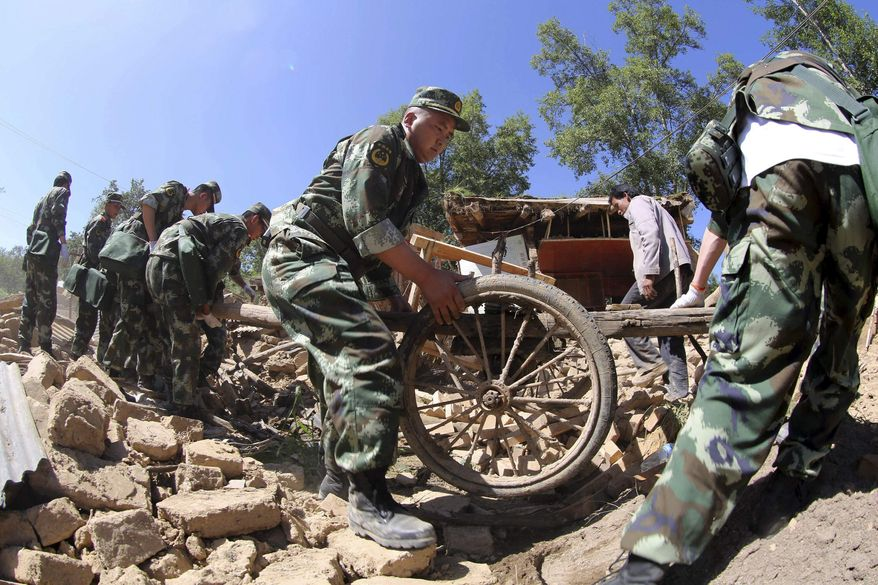 Chinese paramilitary policemen helps residents remove belongings from quake-damaged houses in Lalu village of Hetuo township in Minxian in northwest China's Gansu province Monday July 22, 2013. (AP Photo)