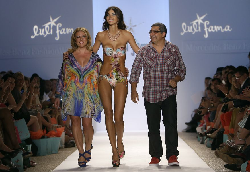 A model walks with Luli Fama designers Lourdes Hanimian, left, and her brother-in-law Augusto Hanimian following their show at Mercedes-Benz Fashion Week Swim, Sunday, July 21, 2013, in Miami Beach, Fla. (AP Photo/Lynne Sladky)