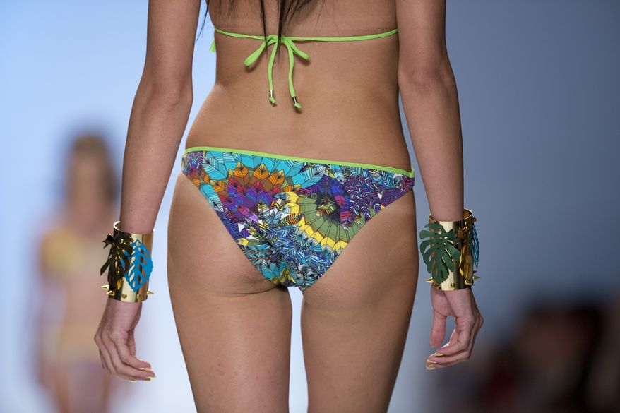 In this Friday, July 19, 2013 photo, a model walks the runway during the Dolores Cortes show at the Mercedes-Benz Fashion Week Swim show in Miami Beach, Fla. (AP Photo/J Pat Carter)