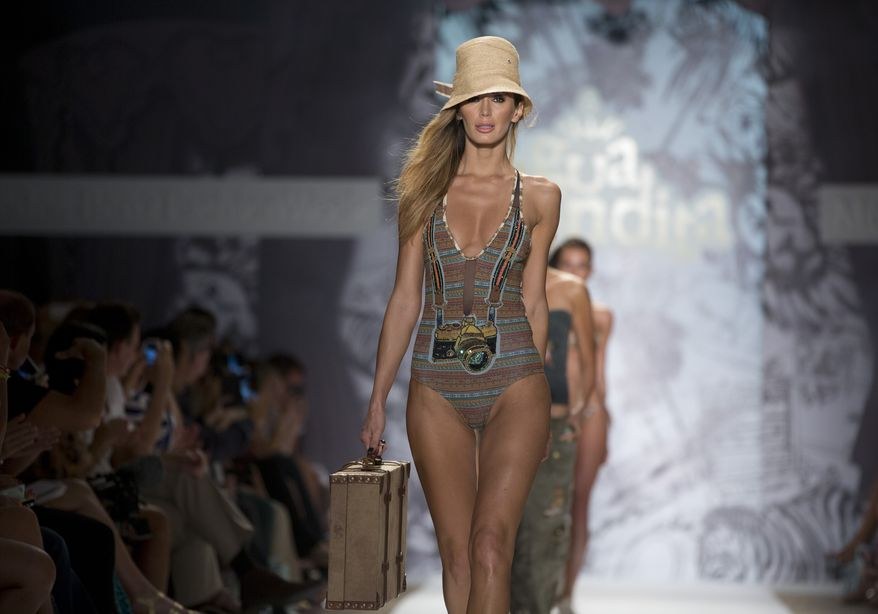 In this Friday, July 19, 2013 photo, a model walks the runway during the Agua Bendita show at the Mercedes-Benz Fashion Week Swim show in Miami Beach, Fla. (AP Photo/J Pat Carter)