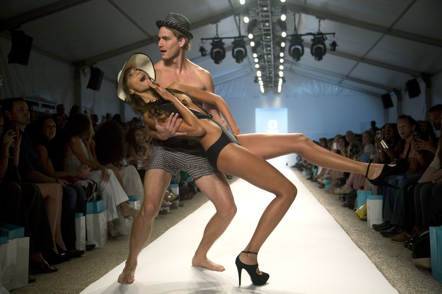 Models pose for photos at the end of the walkway during the Naila show at the Mercedes-Benz Fashion Week Swim show in Miami Beach, Fla., Monday, July 22, 2013. (AP Photo/J Pat Carter)