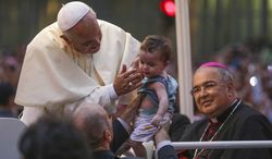 In this photo released by Prefeitura do Rio, a member of security holds up a baby to Pope Francis as he rides in his popemobile into central Rio de Janeiro, Brazil, Monday, July 22, 2013. The pontiff arrived for a seven-day visit in Brazil, the world's most populous Roman Catholic nation. At right is the Rio Archbishop Orani Joao Tempesta. (AP Photo/Raphael Lima, Prefeitura do Rio)