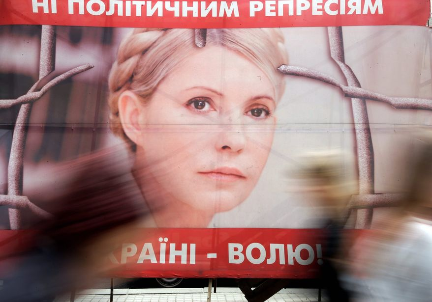 People pass by a poster of Ukraine's imprisoned former Prime Minister Yulia Tymoshenko at a tent camp of her supporters in Kiev. Human rights groups have described the charges against Mrs. Tymoshenko as politically motivated. (Associated Press)