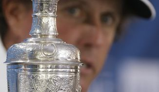 With the Claret Jug trophy in the foreground, Phil Mickelson of the United States talks during a press conference after winning the British Open Golf Championship at Muirfield, Scotland, Sunday July 21, 2013. (AP Photo/Jon Super)