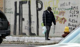 ** FILE ** A pedestrian walks by graffiti in downtown Detroit in a Dec. 12, 2008, file photo. Detroit became the largest city in U.S. history to file for bankruptcy on Thursday, July 18, 2013, when state-appointed emergency manager Kevyn Orr asked a federal judge for municipal bankruptcy protection. (AP Photo/Carlos Osorio, File)