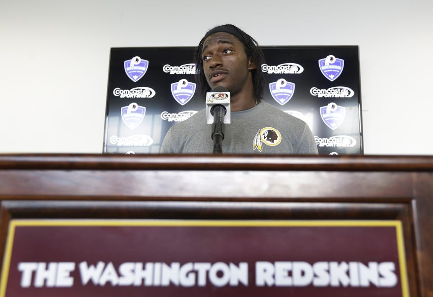 Washington Redskins quarterback Robert Griffin III answers reporters' questions during a news conference at the team's new training facility in Richmond, Va. Wednesday, July 24, 2013. Griffin was recently cleared by doctors to begin practice at NFL football training camp which begins Thursday. (AP Photo/Steve Helber)