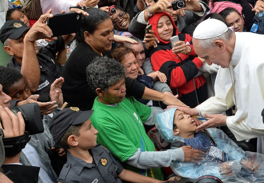 Pope Francis blesses a child during his visit to the Varginha slum in Rio de Janeiro, Brazil, Thursday, July 25, 2013. Francis on Thursday visited one of Rio de Janeiro's shantytowns, or favelas, a place that saw such rough violence in the past that it's known by locals as the Gaza Strip. (AP Photo/Luca Zennaro, Pool)