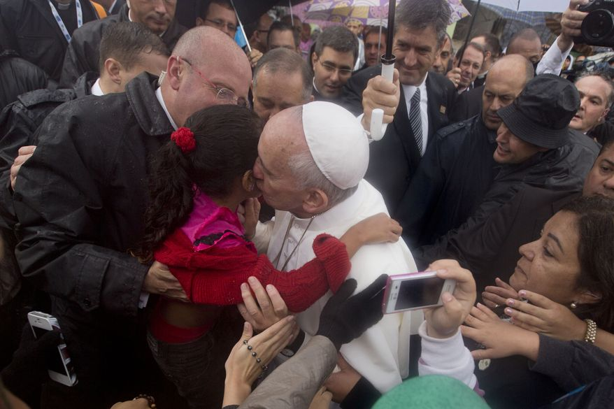 Pope Francis kisses a girl as he visits residents of the Varginha slum in Rio de Janeiro, Brazil, Thursday, July 25, 2013. Francis on Thursday visited one of Rio de Janeiro's shantytowns, or favelas, a place that saw such rough violence in the past that it's known by locals as the Gaza Strip.  (AP Photo/Victor R. Caivano)