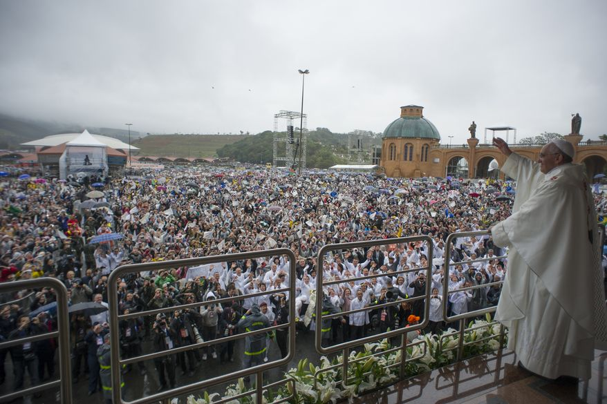 In this photo provided by the Vatican newspaper L'Osservatore RomanoPope Francis waves to pilgrims as he stands on a balcony at the Aparecida Basilica after celebrating Mass in Aparecida, Brazil, Wednesday, July 24, 2013.  Tens of thousands of faithful flocked to the tiny town of Aparecida, tucked into an agricultural region halfway between Rio de Janeiro and Sao Paulo, where he is to celebrate the first public Mass of his trip in a massive basilica dedicated to the nation's patron saint. (AP Photo/L'Osservatore Romano)