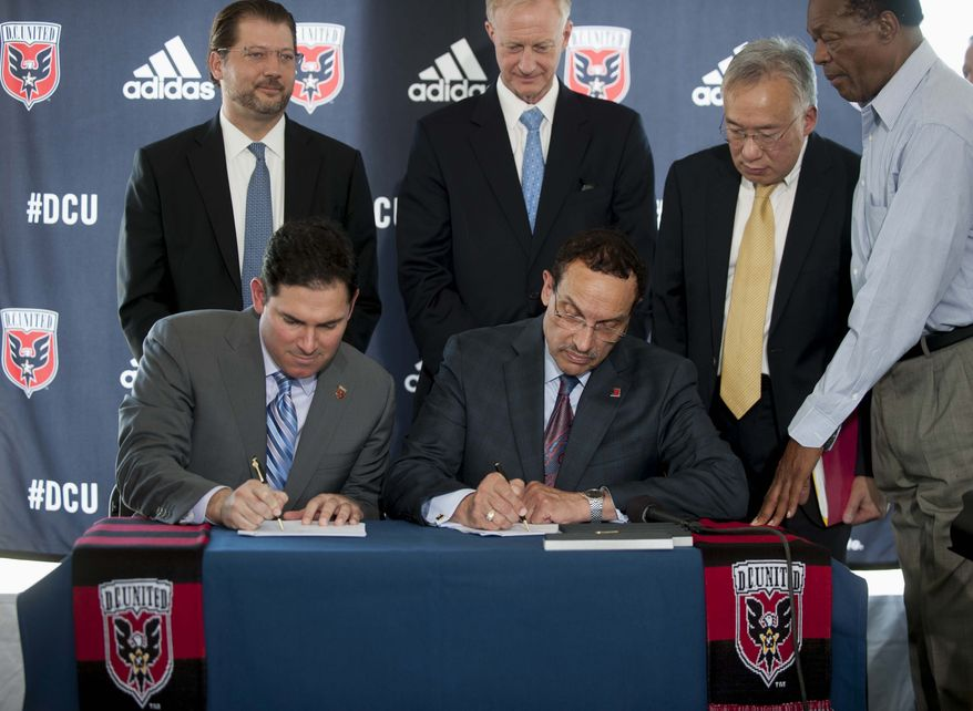 DC United soccer Managing Partner Jason Levien, seated left, and Washington Mayor Vincent Gray, seated right, sign a public-private partnership to build a soccer stadium during a news conference in Washington, Thursday, July 25, 2013. DC United and city officials have agreed to a deal that would keep the Major League Soccer franchise in the District of Columbia with a new, $300 million soccer-only stadium. (AP Photo/Kevin Wolf )